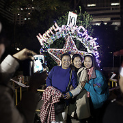 Hong Kong has a huge population of Filipinos, mostly woman who work as domestic workers in the business community. Here Filipino women celebrate Christmas together out door in downtown Hong Kong, most Filipinos are Catholics.   <br />