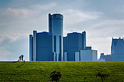 People on a grassy knoll in the Tricentennial Park in Detroit, with the General Motors Headquarters in the background. Detroit bankruptcy.
