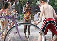 (Boston, MA - August 16, 2009) - Ifeoma Linda Onyenwe, 7 of Lowell (center), plays in the fountain on the Rose Kennedy Greenway downtown on Sunday afternoon where temperatures reached into the low 90s. ..Herald photo by Will Nunnally