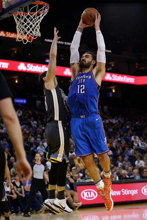 Oklahoma City Thunder center Steven Adams (12) dunks against Golden State Warriors forward Omri Casspi (18) during the second half of an NBA game between the Warriors and Oklahoma City Thunder at Oracle Arena, Tuesday, Feb. 6, 2018, in Oakland, Calif. The Warriors lost 105-125.