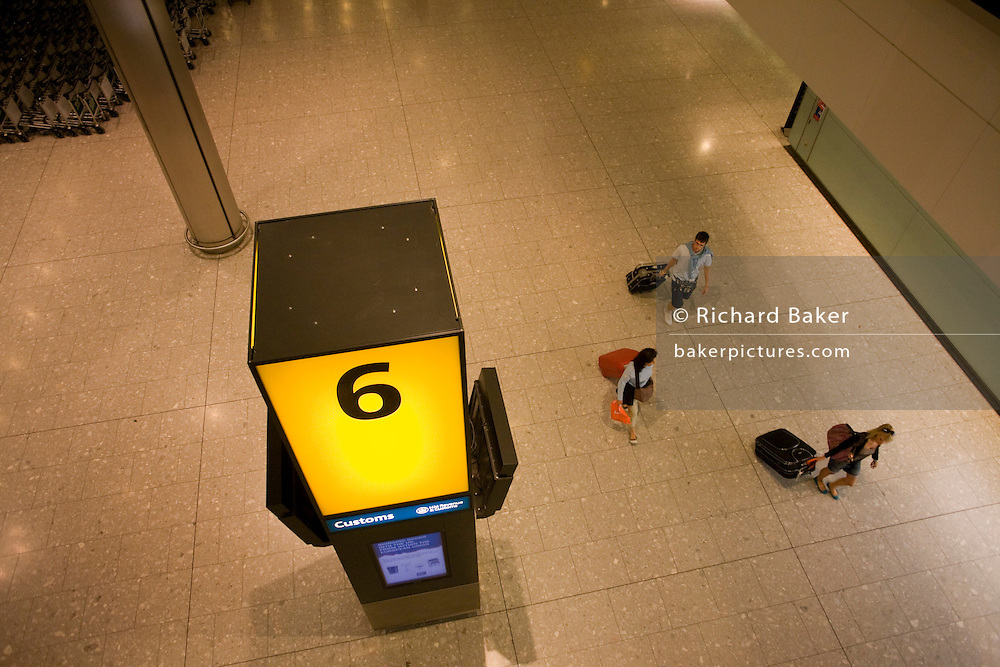 Aerial view of passengers towing wheelie baggage in the baggage reclaim hall in the arrivals of Heathrow Airport's T5