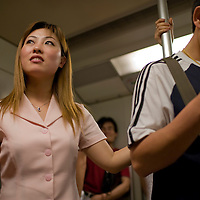 Asia, China, Shanghai, Young Chinese woman standing while riding on Metro subway train during evening rush hour