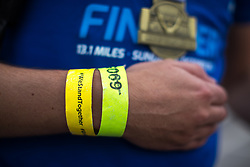 "© Licensed to London News Pictures . 15/10/2017 . Manchester , UK . Athlete with a "" We Stand Together "" wristband reaches the finish line in the Greater Manchester Half Marathon in Old Trafford . Photo credit : Joel Goodman/LNP"