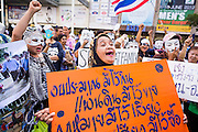 """09 JUNE 2013 - BANGKOK, THAILAND:  A Thai Muslim woman who is a member of the White Masks protests against the government of Yingluck Shinawatra at Central World. The White Mask protesters wear the Guy Fawkes mask popularized by the movie """"V for Vendetta"""" and the protest groups Anonymous and Occupy. Several hundred members of the White Mask movement gathered on the plaza in front of Central World, a large shopping complex at the Ratchaprasong Intersection in Bangkok, to protest against the government of Thai Prime Minister Yingluck Shinawatra. They say that her government is corrupt and is a """"puppet"""" of ousted (and exiled) former PM Thaksin Shinawatra. Thaksin is Yingluck's brother. She was elected in 2011 when her brother endorsed her.     PHOTO BY JACK KURTZ"""