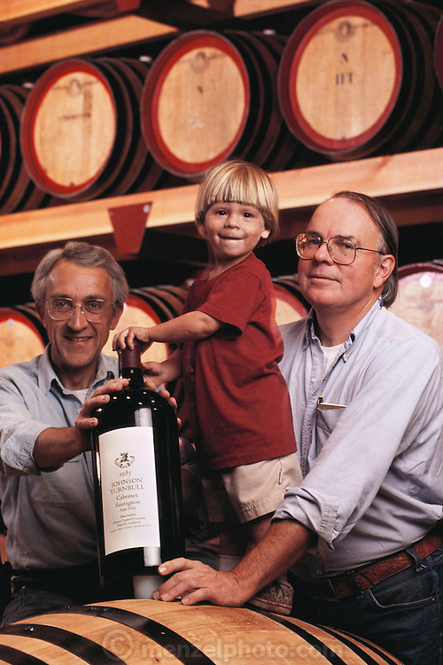 Johnson Turnbull Winery co-founders, Reverdy Johnson (attorney) and Bill Turnbull (architect), and son Andrew Turnbull, in the barrel cellar of the winery. Mr. Johnson is holding a 6-liter bottle of Cabernet Sauvignon; their best known wine.  The winery was purchased in 1992 by Patrick O'Dell and renamed Turnbull Winery. Photographed in 1990.  Oakville, Napa, Valley, California. MODEL RELEASED.