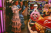 Two young girls dressed in traditional Spanish flamenco attire stop at the childrens' fairground during a lull in the celebrations for the April Feria, Seville. A pair of eyes painted on the front of the train ride engine looks across to one of the girls' similarly-designed dress. It is part of a lively event that Seville holds annually in the vast area on the far bank of the Guadalquivir River. Rows of temporary marquee tents, or casetas, host families, corporations and friends into the late hours during the April Fair which begins begins two weeks after the Semana Santa, or Easter Holy Week in the Andalusian capital.