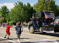 Rusty's Towing tosses candy to the children in the crowd during Laconia's 4th of July parade on Tuesday.  (Karen Bobotas/for the Laconia Daily Sun)
