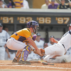 Tony Asaro #53 of UC Irvine slides in front of the tag by LSU catcher Micah Gibbs #33 in the bottom of the 4th inning.  The LSU Tigers defeated the UC Irvine Anteaters 9-7 with a ninth inning rally in game two of a three game NCAA Baseball Super Regional playoff at Alex Box Stadium in Baton Rouge, LA..