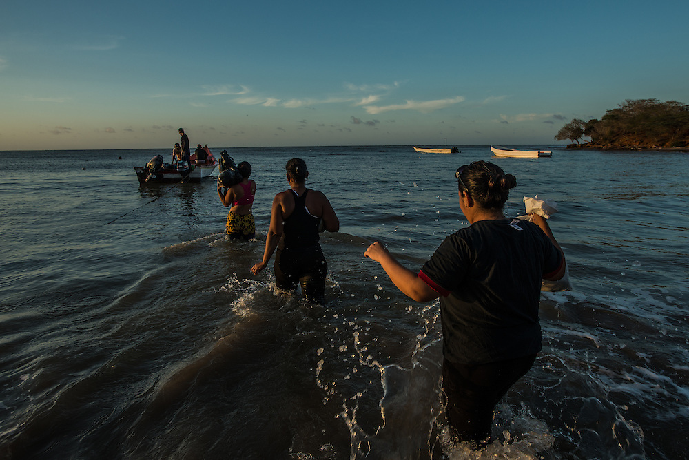 FALCÓN, VENEZUELA - SEPTEMBER 26, 2016: Undocumented migrants on the beach just before boarding the smuggler's boat that will illegally take them from Venezuela to Curaçao. Undocumented migrants here have mortgaged property, sold kitchen appliances and even borrowed money from the same smuggling rings that pack them on the floorboards alongside drugs and other contraband. The journey to Curaçao takes them on a 60-mile crossing filled with backbreaking swells, gangs of armed boatmen and coast guard vessels looking to capture migrants and send them home. Then, after being tossed overboard and left to swim ashore, they hide in the brush to meet contacts who spirit them anew into the tourist economy of this Caribbean island. They clean the floors of restaurants, work in construction, sell trinkets on the street, or even solicit Dutch tourists for sex. But at least, the migrants say, there is food. PHOTO: Meridith Kohut
