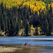 A lone kayaker enjoys the Fall foliage and the peaceful solitude on Lost Lake Slough near Kebler Pass, Colorado.