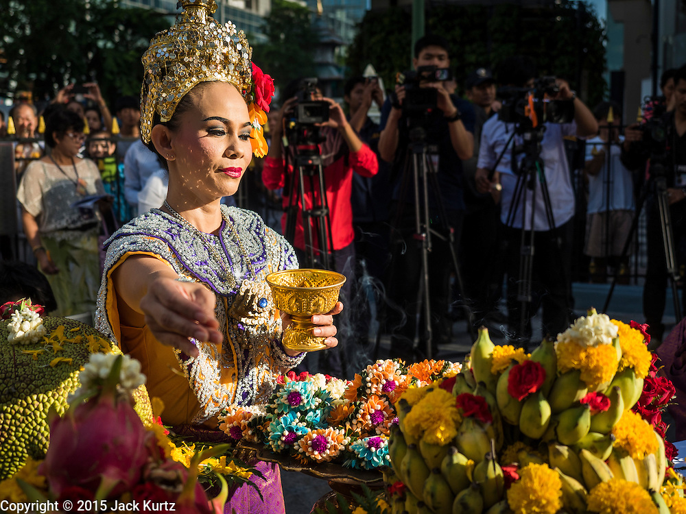 """04 SEPTEMBER 2015 - BANGKOK, THAILAND:  A Thai dancer makes an offering durinf a blessing ceremony at the Erawan Shrine Friday. A """"Holy Religious Ceremony for Wellness and Prosperity of our Nation and Thai People"""" was held Friday morning at Erawan Shrine. The ceremony was to regain confidence of the Thai people and foreign visitors, to preserve Thai religious customs and traditions and to promote peace and happiness inThailand. Repairs to Erawan Shrine were completed Thursday, Sept 3 after the shrine was bombed on August 17. Twenty people were killed in the bombing and more than 100 injured. The statue of the Four Faced Brahma in the shrine was damaged by shrapnel and a building at the shrine was damaged by debris.    PHOTO BY JACK KURTZ"""