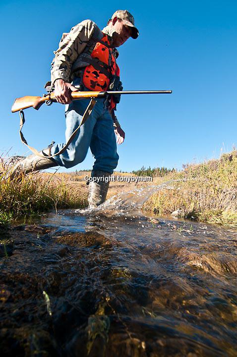 hunter crossing creek in grass field wild rocky mountains deer rifle