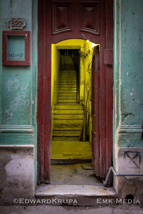 An open apartment entrance that leads to a stairway in Havana.