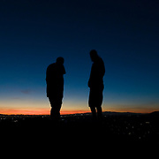 Hikers watch the sunset from Camelback Mountain in Phoenix, Arizona