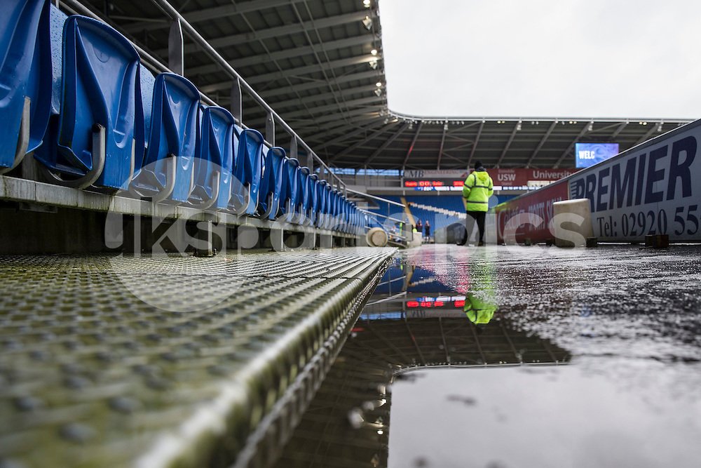 A steward is reflected in a puddle ahead of the Sky Bet Championship match between Cardiff City and Burnley at the Cardiff City Stadium, Cardiff, Wales on 28 November 2015. Photo by Mark Hawkins.