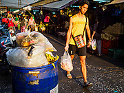 "04 DECEMBER 2018 - BANGKOK, THAILAND: A shopper walks past garbage wrapped in single use plastic bags in Khlong Toei market. The issue of plastic waste became a public one in early June when a whale in Thai waters died after ingesting 18 pounds of plastic. In a recent report, Ocean Conservancy claimed that Thailand, China, Indonesia, the Philippines, and Vietnam were responsible for as much as 60 percent of the plastic waste in the world's oceans. Khlong Toey (also called Khlong Toei) Market is one of the largest ""wet markets"" in Thailand. December 4 was supposed to be a plastic free day in Bangkok but many market venders continued to use plastic.    PHOTO BY JACK KURTZ"