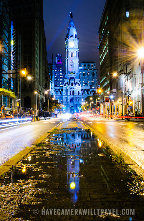 City Hall as seen from Broad Street after rain with traffic streaks. City Hall is reflected in the water puddle in the center of the frame