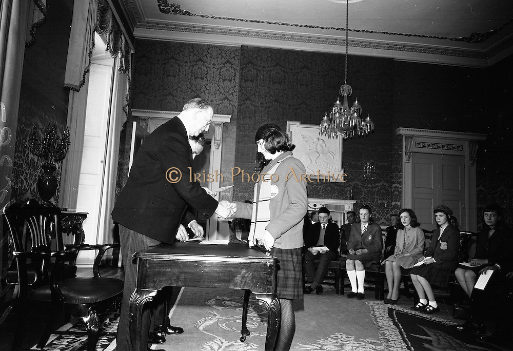 28/04/1966<br /> 04/28/1966<br /> 28 April 1966<br /> President Eamon de Valera presents prizes at Aras an Uachtarain. The President presented the prizes to the winners of competitions for schoolchildren organised by the Golden Jubilee 1916 Committee. The winners from schools all over Ireland competed in competitions for essays and poetry in Irish and English. Picture shows President de Valera presenting 2st prize of £30 in competition of Irish original Poetry to Cáit Nic Ghearailt, Baile an MMhordaigh, Baile na nGall, Trailí, Co. Cherri, a pupil of Colaiste Íde, Daingean.