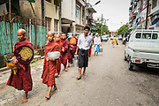 "13 JUNE 2013 - YANGON, MYANMAR:  Buddhist monks walk down a street in Yangon soliciting alms and donations. Most men in Myanmar join the ""Sangha"" (clergy) at least once in their life. Some stay monks for just a few weeks, others for year and a few make it a life time commitment. Yangon, formerly Rangoon, is Myanmar's commercial capital and used to be the national capital. The city is on the Irrawaddy River and has a vibrant riverfront.    PHOTO BY JACK KURTZ"