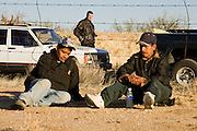02 APRIL 2006 - THREE POINTS, AZ: Undocumented Mexican immigrants from the Mexican state of Veracruz, sit in the desert in front of a Minuteman Project observation post on the King's Anvil Ranch during the Minuteman Project action between Three Points, AZ, and Sasabe, AZ, about 50 miles south of Tucson, AZ, April, 2, 2006. Volunteers from the Minuteman Project have set up a line of about 20 observation posts on King's Anvil Ranch, a cattle ranch in the area. On Saturday night, the first night of the action, the Minuteman volunteers spotted more than 50 illegal immigrants, they claim their tips to the US Border Patrol led to the apprehension of at least 16 of those immigrants.  Photo by Jack Kurtz