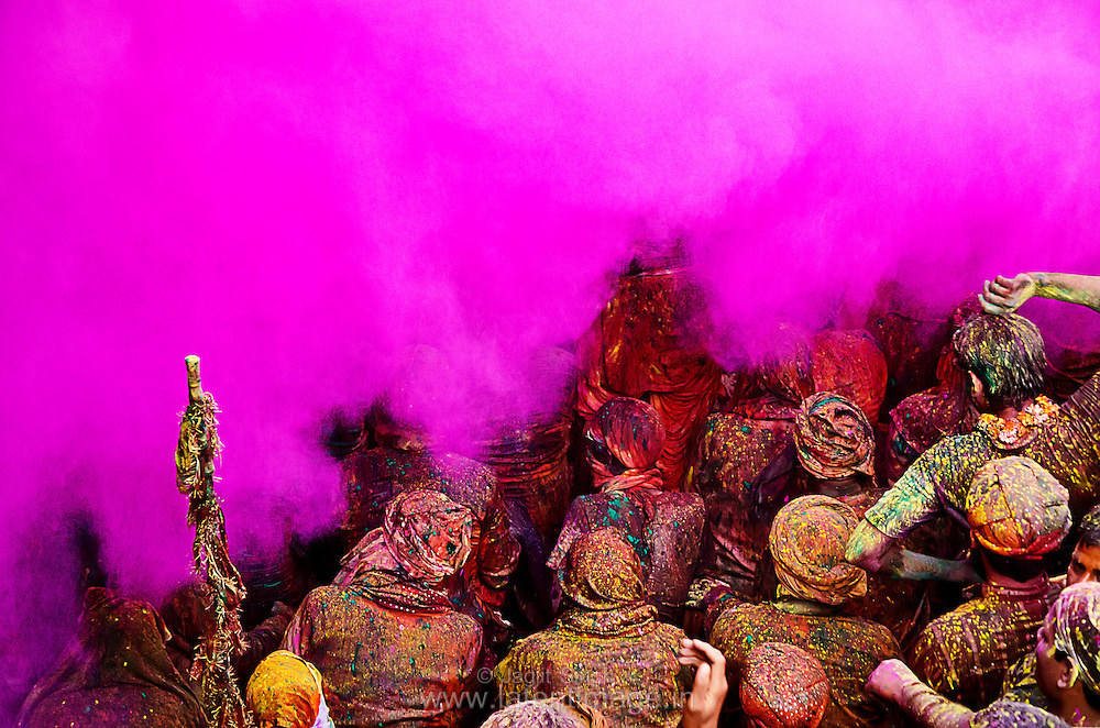 Samaj at Radha Rani temple, Barsana. People sing loudly in a very colorful environment. Dry and wet colors splashed on them from all corners of the temple. A cloud of pink color approaching. Braj ki Holi