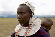 Masai mother carrying child on her back, in the forest the Ngorongoro Conservation Area or NCA is a conservation area situated 180 km west of Arusha in the Crater Highlands area of Tanzania.