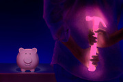 Man with glowing pink hammer approaches an unsuspecting piggy bank.Black light