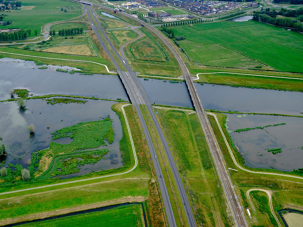 "Nederland, Overijssel, Gemeente Kampen; 21–06-2020; het Reevediep ter plaatse van Reevediepbrug (rijksweg N50) en Spoorbrug Reevediep, station Kampen-Zuid in de achtergrond.<br /> Het Reevediep is aangelegd in het kader van het project Ruimte voor de Rivier om bij hoogwater water af te voeren voordat dit het nabij gelegen Kampen bereikt, direct naar het IJsselmeer, de 'bypass Kampen'. Het Reevediepgebied is ook een natuurgebied en vormt een ecologische verbindingszone tussen rivier de IJssel en Drontermeer.<br /> Reevediep at the location of the Reevediep Bridge (national road N50) and the Reevediep Railway Bridge, Kampen-Zuid station in the background. The Reevediep has been constructed as part of the Room for the River project, and functions to discharge high waters before reaching the nearby Kampen, directly to the IJsselmeer, the ""bypass Kampen"". The Reevediep area is also a nature reserve and forms an ecological connecting zone between the river IJssel and Drontermeer.<br /> <br /> luchtfoto (toeslag op standaard tarieven);<br /> aerial photo (additional fee required)<br /> copyright © 2020 foto/photo Siebe Swart"