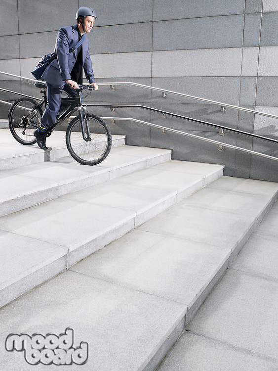 Business man wearing crash helmet riding bicycle down steps side view