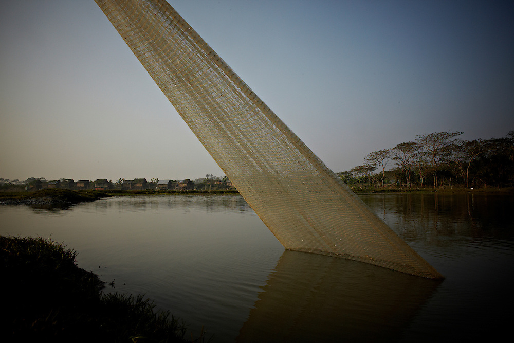 The fishing net of Taher Hussein. in september 2008 he had to move to the second floor of his house due to heavy flooding. in the background is the embankment.. ?This area in the south of Bangladesh has been called ground zero of climate-change due to heavy river and ocean erosion. The lowlying area is also hugely affected by cyclones and rising sea-levels...By the Mouth of Ganges, at the Bay of Bengal is the Island of Bhola. This home of about two million people is considered to be ground zero of climate change. Half the island has disappeared in the past 40 years, and according to scientists the pace is not going to slow down. People pack up and leave as the water get closer. Some to a nearby embankment, while those with enough money move further inland, but for most life move on until the inevitable. It's always about survival for the people in one of the worlds poorest countries...Photo by: Eivind H. Natvig/MOMENT