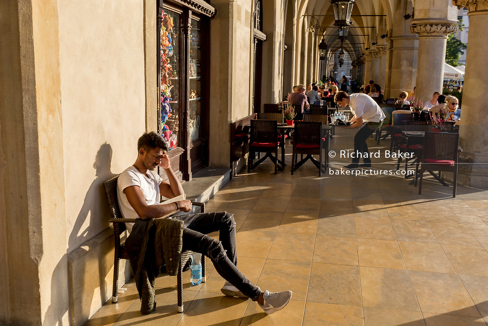 A young man reads a book in afternoon sunshine in the arched passageway of the Renaissance Cloth Hall on Rynek Glowny market square, on 22nd September 2019, in Krakow, Malopolska, Poland.