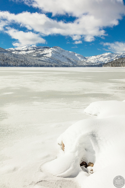 """""""Snow Covered Donner Lake 2"""" - Photograph of a mostly iced over and snow covered Donner Lake, Donner Summit can be seen in the background."""