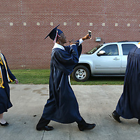 Baldwyn High School senior Jacolby Bowdry takes a video on his cell phone as he and his classmates walk to the gym before the start of Friday night's graduation ceremony at the school.