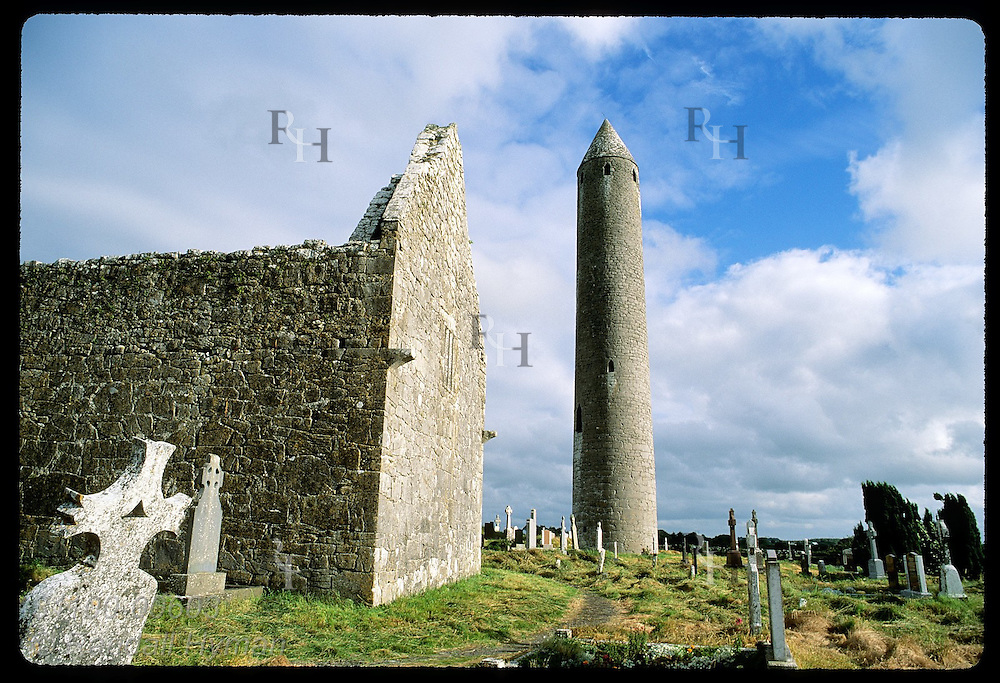 Cathedral wall frames 112' round tower @ Kilmacduagh, St. Colman monastery site of 6th-c; Gort. Ireland