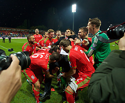 ZENICA, BOSNIA & HERZEGOVINA - Saturday, October 10, 2015: Wales' players grab manager Chris Coleman to celebrate qualifying for the Euro 2016 finals despite a 2-0 defeat to Bosnia and Herzegovina during the UEFA Euro 2016 qualifying match at Stadion Bilino Polje. (Pic by David Rawcliffe/Propaganda)