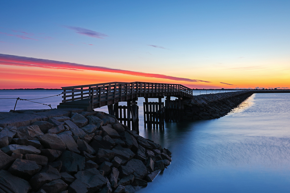 Seascape photography of the harbor jetty with its wooden bridge at dawn in Plymouth, MA. The town of Plymouth is most famous for its historic landmarks and sites such as Plymouth Rock, the Mayflower and Plimoth Plantation. <br />