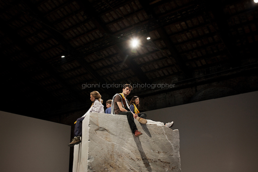 VENICE, ITALY - 30 MAY 2013: Marcello Maloberti's <br /> &quot;La voglia matta&quot;  (2013) -<br /> block of marble, beach towels, fanzine - Atop a large block of marble, four performers raise<br /> and lower beach towels at regular intervals, at the Italian Pavillon, at the Arsenale in Venice, Italy, on May 30th 2013. <br /> <br /> The Italian Pavilion presents vice versa, an ideal journey through Italian art of today,<br /> an itinerary that tells of identities, history and landscapes - real and imaginary - exploring the complexity and layers that characterize the country's artistic vicissitudes. The Italian Pavillon is curated by Bartolomeo Pietromarchi,<br /> who describes the exhibition as, ?A portrait of recent art, read as an atlas of themes and attitudes in dialogue with the historical legacy and current affairs, with both a local and international dimension. A cross-dialogue of correspondences, derivations and differences between acclaimed maestros and artists of later generations&quot;. The exhibition is divided into seven spaces - six rooms and a garden - that each house<br /> the work of two artists,<br /> who are brought together on the basis of the affinity of their<br /> respective poetics and common interests in themes, ideas and practices.<br /> <br /> The 55th International Art Exhibition of the Venice Biennale takes place in Venice from June 1st to November 24th, 2013 at the Giardini and at the Arsenale as well as in various venues the city. <br /> <br /> Gianni Cipriano for The New York TImes