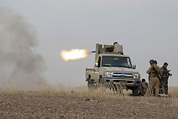 © Licensed to London News Pictures. 30/09/2015. Kirkuk, Iraq. Kurdish peshmerga fighters fire a heavy machine gun into the village of Mansoria during an offensive aimed at capturing 11 villages from the Islamic State near Kirkuk, Iraq.<br /> <br /> Supported by large amounts of coalition airstrikes, members of the Iraqi-Kurdish peshmerga today (30/09/2015) took part in an offensive to take seven villages across a large front near Kirkuk, Iraq. By mid afternoon the Kurds had reached most of their objectives, but suffered around 10 casualties all to improvised explosive devices. All seven villages were originally Kurdish and settled with other ethnic groups during the Iraqi Arabisation process of the 1970's and 80's. Photo credit: Matt Cetti-Roberts/LNP