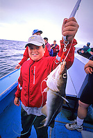 Boy,10, holds up a cod fish on a boat off PEI.