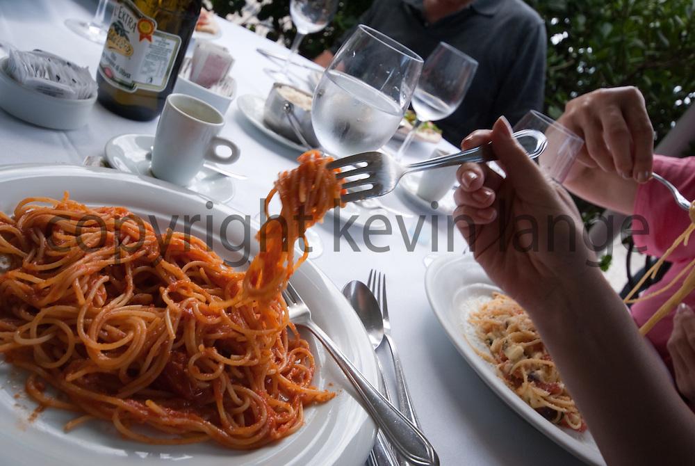 crop of woman's hand eating spaghetti while visiting copacabana in rio de janeiro, brazil.