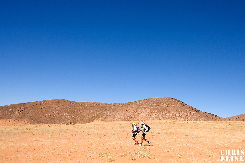 27 March 2007: Two participants run across sandy hilly areas near jebel Zireg during third stage of the 22nd Marathon des Sables between jebel El Oftal and jebel Zireg (20.07 miles). The Marathon des Sables is a 6 days and 151 miles endurance race with food self sufficiency across the Sahara Desert in Morocco. Each participant must carry his, or her, own backpack containing food, sleeping gear and other material.