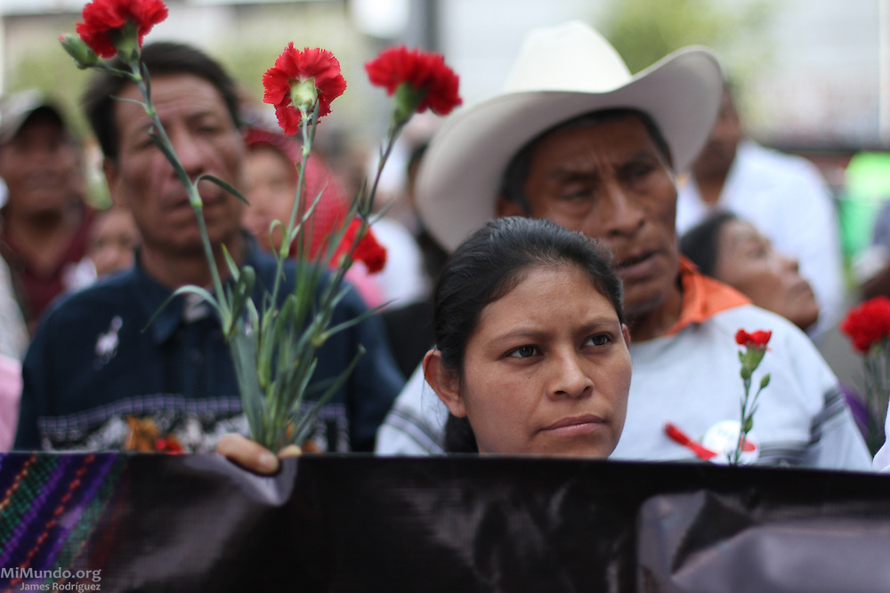 People hold red carnations, symbols of wartime victims, as they get ready to march to the Constitutional Court. Despite the trial's suspension ordered by High Risk Court Judge Carol Flores on the previous day, Judge Jazmin Barrios reconvened the trial on the 21st day to decide on a course of action. Judge Barrios ruled that Judge Flores' annulment is illegal and will be asking the Constitutional Court, Guatemala's highest judicial body, to rule on the fate of the genocide trial. Guatemala, Guatemala. April 19, 2013.