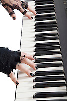 Cropped image of female fingers playing piano keyboard