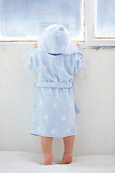 Back view of Baby Boy Standing on Bed Wearing Bathrobe