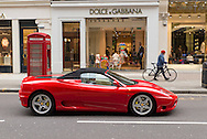 A Ferrari in front of a Dolce & Gabbana store in Knightsbridge, an exclusive area of London. Notice the telephone box which has been turned into a cash machine.