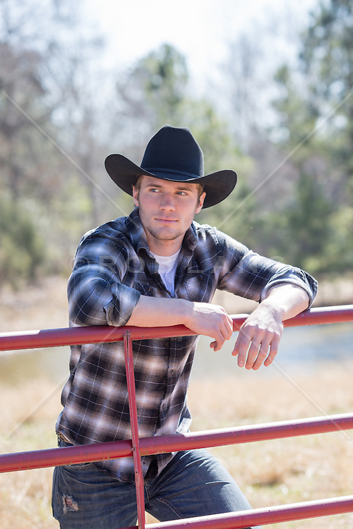 cowboy leaning on a fence on a ranch