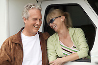 Smiling mature couple next to RV