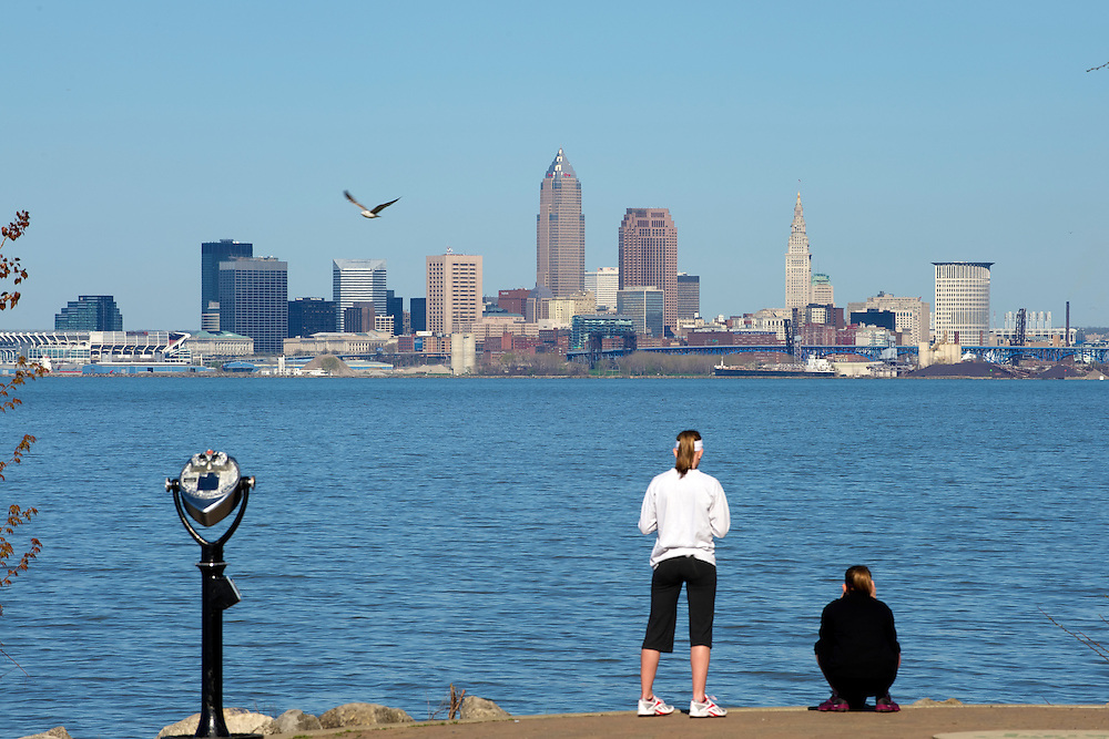 A view of the Cleveland skyline from Lakewood park with people and Lake Erie in the foreground.