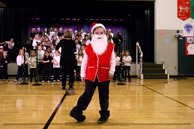 With student artwork on the walls, Ben Marsh is a dancing Santa while Ms. Criss directs the Singing Colts as they sing Santa Claus is on His Way during the 'We Will Jingle!' arts concert at Cleveland PK-8 school in Dayton, Wednesday, December 12, 2012.