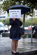 Frankfurt am Main | 08 Oct 2014<br /> <br /> Am Mittwoch (08.10.2014) nahmen an der Konstablerwache in der Innenstadt von Frankfurt am Main etwa 100 Menschen an einer Kundgebung f&uuml;r Solidarit&auml;t mit der von IS (ISIS, ISIL, Islamischer Staat) angegriffenen Stadt Kobane (auch: Ain al-Arab) teil. Die kundgebung verlief friedlich, es kam nur zu einer kleinen St&ouml;rung durch einen jungen Moslem, der sich durch einen Redebeitrag in seinem Glauben beleidigt f&uuml;hlte.<br /> Hier: Eine Frau mit einem Transparent mit der Aufschrift &quot;Kobane ist nicht allein&quot;.<br /> <br /> &copy;peter-juelich.com<br /> <br /> [No Model Release | No Property Release]